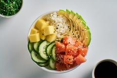 Raw Organic Poke Bowl with salmon, avocado, rice, mango, cucumbers, chuka salad and soy sauce close-up on white table background. stock image
