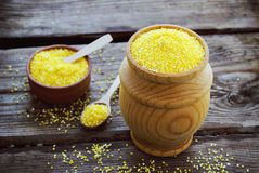 Raw organic polenta corn meal in a wooden bowl. Selective focus royalty free stock photo