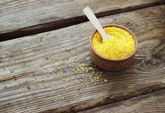 Raw organic polenta corn meal in a wooden bowl Royalty Free Stock Photos
