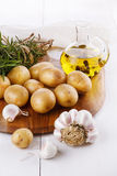 Raw organic potato with rosemary and garlic over white backgroun. Fresh organic potato with rosemary, garlic and oil on a chopping board over white wooden stock photo