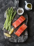 Raw organic salmon and young green asparagus on a rustic chopping board on a dark background, top view. Food ingredients