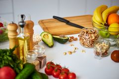 Raw organic vegetables, fruits and nuts with fresh ingredients for healthily cooking on kitchen. Vegan or diet food concept. royalty free stock photo