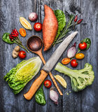 Raw organic vegetables with kitchen knife and selection wooden spoon. Ingredients for healthy cooking on rustic wooden background. Raw organic vegetables with stock photos