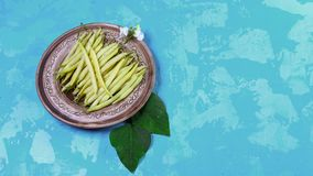 Raw Organic Yellow bean pods on a plate on a blue background. Copy Space for Text. Website Banner Poster Template. Vegetarian Supe. Foods stock photo