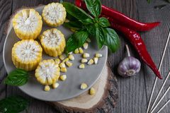 Raw Organic Yellow Corn on the Cob Ready to grill with hot chili pepper garlic and herbs. Royalty Free Stock Image