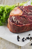 Raw Osso Bucco. Raw Moose Meat. Osso Bucco with Rucola, Peppers and Juniper Berries. Shallow Depth of Field Royalty Free Stock Image