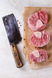 Raw osso buco. Meat on crumpled paper with salt, pepper and rosemary. With vintage backsword over white marble as background. Top view Stock Photography