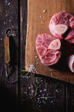 Raw osso buco. Meat on wooden cutting board with vintage steelyard, salt, pepper and rosemary over old wooden table. Dark rustic style. Top view Stock Photos