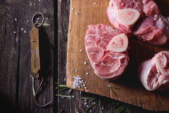 Raw osso buco. Meat on wooden cutting board with vintage steelyard, salt, pepper and rosemary over old wooden table. Dark rustic style. Top view Stock Photo