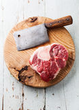 Raw Ossobuco and meat cleaver. Raw fresh cross cut veal shank for making Ossobuco and meat cleaver on wooden cutting board royalty free stock photography