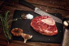 Raw ossobuco on a stone base for the meat. Royalty Free Stock Photography