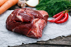 Raw Ox Cheek on crumpled paper,  decorated with greens and vegetables. on old  wooden table.  Royalty Free Stock Images