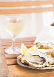 Raw oysters shells. And glass of white wine Stock Photo