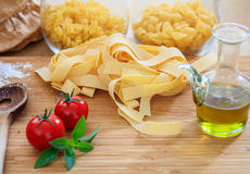Raw pappardelle pasta with tomatoes and basil. On a wooden surface Stock Images