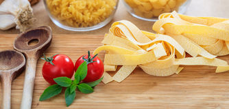 Raw pappardelle pasta with tomatoes and garlic. Raw pappardelle pasta with tomatoes, garlic and wooden ladles Stock Photo
