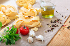 Raw pappardelle pasta with vegetables. And olive oil Royalty Free Stock Photo
