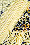 Raw Pasta. Vertical frame of uncooked pasta on dark background Stock Photography
