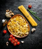 Raw pasta assortment with rosemary,tomatoes and mushrooms. On black rustic background royalty free stock image