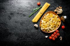 Raw pasta assortment with rosemary,tomatoes and mushrooms. On black rustic background stock images