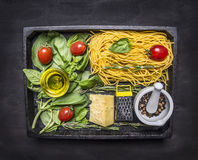 Raw pasta with basil, cherry tomatoes, butter, cheese grater and cheese, whole pepper in a mortar  wooden box on wooden rustic Royalty Free Stock Images
