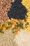 Raw pasta, beans, lentils and rice as a background. Raw pasta, beans, lentils and rice laid out as a background pattern Stock Photo