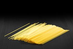 Raw pasta on black table Stock Image