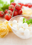 Raw pasta in a bowl and mozzarella, cherry tomatoes Royalty Free Stock Photography