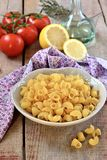 Raw pasta in a bowl with olive oil, lemon and tomatoes Stock Photography