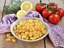 Raw pasta in a bowl with olive oil, lemon and tomatoes. Pasta in a bowl with olive oil, lemon and tomatoes on wooden background Royalty Free Stock Image