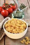 Raw pasta in a bowl with olive oil and tomatoes. Pasta in a bowl with olive oil on wooden background Stock Images
