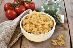 Raw pasta in a bowl with olive oil and tomatoes. Pasta in a bowl with olive oil on wooden background Royalty Free Stock Images