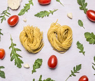 Raw pasta cherry tomatoes arugula heads of garlic  white rustic  wooden background top view Royalty Free Stock Image
