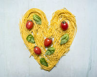 Raw pasta with cherry tomatoes and basil leaves lined heart, valentines day on wooden rustic background top view close up Royalty Free Stock Photos