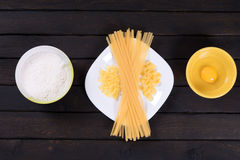 Raw pasta on a dark table, egg, flour. Top view stock photos