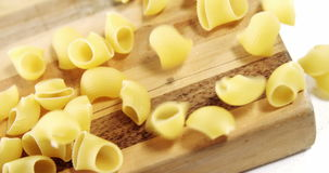 Raw pasta falling on chopping board. Close-up of raw pasta falling on chopping board stock footage