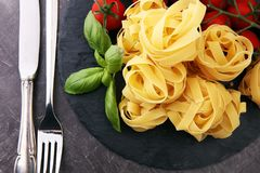 Raw pasta and fresh red cherry tomatoes with basil.  Stock Image