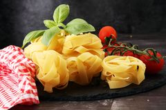 Raw pasta and fresh red cherry tomatoes with basil.  Royalty Free Stock Images