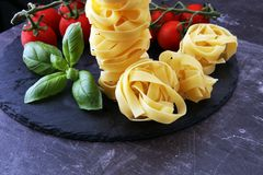 Raw pasta and fresh red cherry tomatoes with basil.  Stock Images