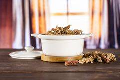 Raw pasta fusilli with curtains. Lot of whole raw pasta fusilli variety in a ceramic stewpan with silk curtains behind royalty free stock image