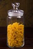 Raw pasta on glass jar Stock Image