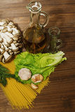 Raw pasta infredients in the kitchen. Variety of pasts ingredients prepared for cooking on the wooden rural style table stock images