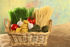 Raw Pasta with Ingredients in Basket. Raw green and yellow tagliatelle paglia e fieno (straw and hay) with raw tomatoes and garlic bulbs (Selective Focus, Focus Stock Image