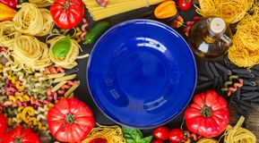 Raw pasta with ingredients and blue plate Royalty Free Stock Photo