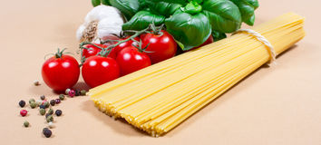 Raw pasta and ingredients for pasta with tomatoes and basil. Raw pasta and ingredients for pasta with tomatoes, garlic, basil and pepper Stock Photos