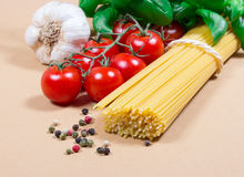 Raw pasta and ingredients for pasta with tomatoes and basil. Raw pasta and ingredients for pasta with tomatoes, garlic, basil and pepper Royalty Free Stock Images