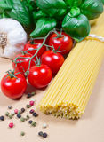 Raw pasta and ingredients for pasta with tomatoes and basil. Raw pasta and ingredients for pasta with tomatoes, garlic, basil and pepper Stock Image