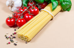 Raw pasta and ingredients for pasta with tomatoes and basil. Raw pasta and ingredients for pasta with tomatoes, garlic, basil and pepper Stock Images