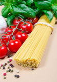 Raw pasta and ingredients for pasta with tomatoes and basil. Raw pasta and ingredients for pasta with tomatoes, garlic, basil and pepper Stock Photo