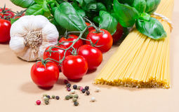 Raw pasta and ingredients for pasta with tomatoes and basil. Raw pasta and ingredients for pasta with tomatoes, garlic, basil and pepper Royalty Free Stock Photo