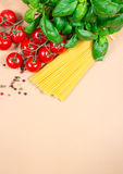 Raw pasta and ingredients for pasta with tomatoes and basil. Raw pasta and ingredients for pasta with tomatoes, basil and pepper Royalty Free Stock Image